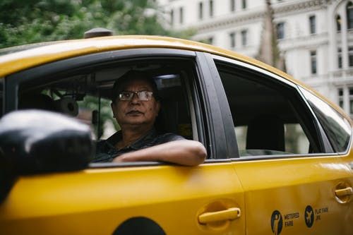 Through window of male driver in glasses sitting in cab while driving in downtown of city and looking away