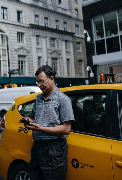 Ethnic man standing near taxi with smartphone