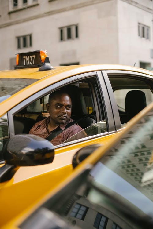 Through window of adult male driver sitting in cab while talking with coworker on modern city street