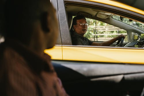 Ethnic men communicating in cars on road