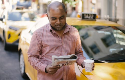 Man with coffee and newspaper near cab