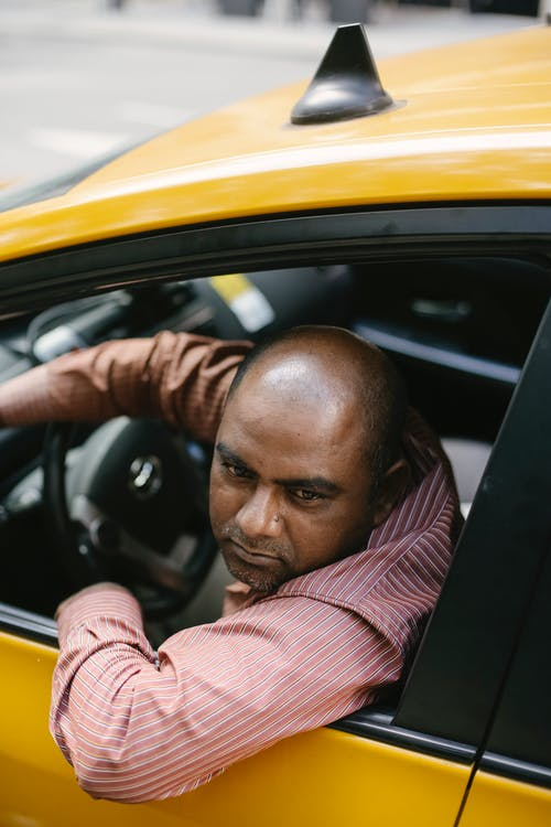 Ethnic man relaxing in taxi on road