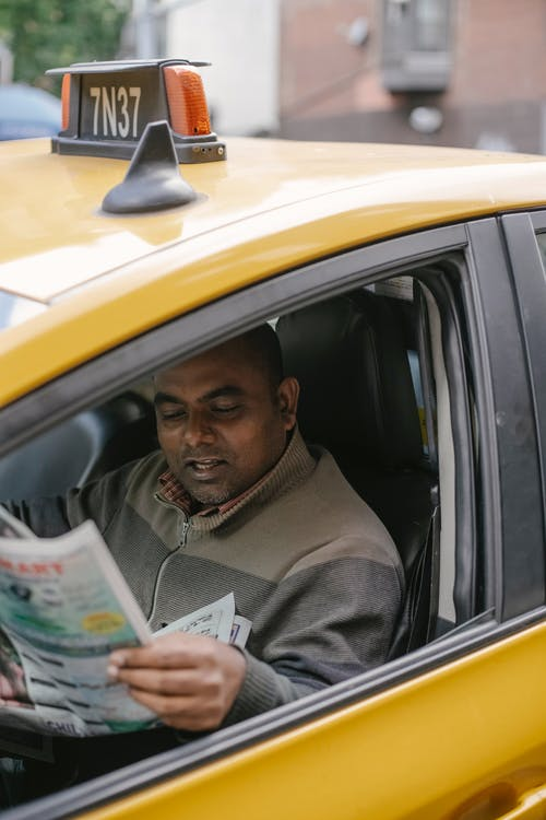 Ethnic male driver sitting in cab on city street while waiting passenger and reading newspaper