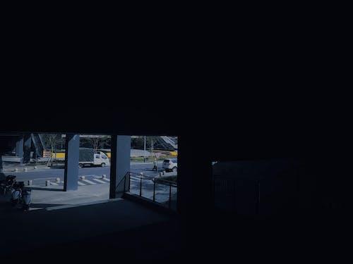 View from dark corner under bridge through pillars on carriageway on sunny day