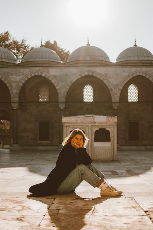 Woman in Black Coat Sitting on Tiled Floor