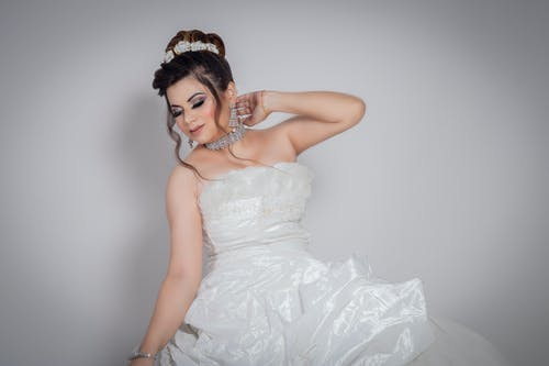 Female model dressed in bridal gown with makeup and jewelry touching neck gently standing against gray background