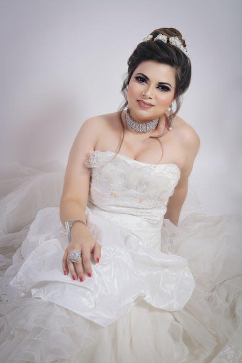 Elegant bride in white dress in studio