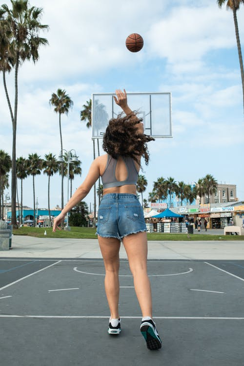 Woman in Blue Denim Shorts Standing on Basketball Court
