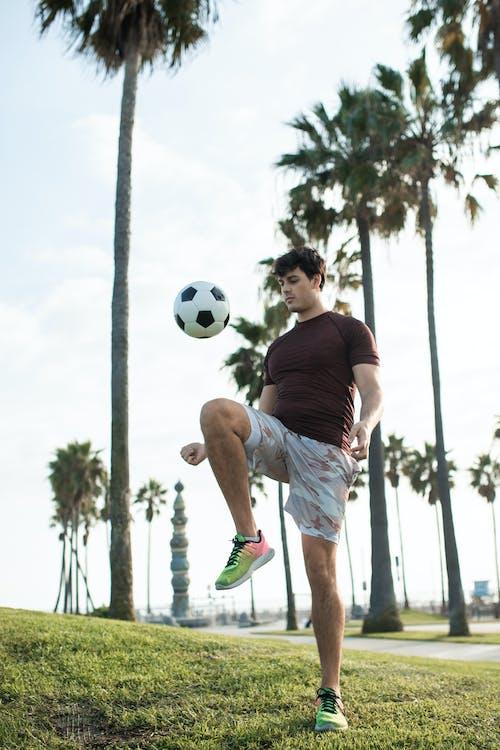 Man In Zwart T Shirt En Witte Broek Te Voetballen