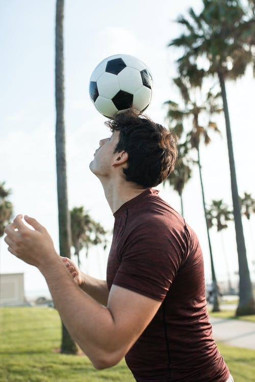 Man in Red T-shirt Holding Soccer Ball