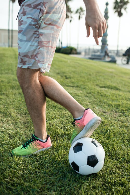 Person in Green and White Nike Soccer Cleats Standing on Green Grass Field