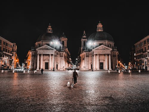 Pedestrians on paved squared near old catholic churches Santa Maria in Montesanto and Santa Maria dei Miracoli with columns at entrance at night in Rome