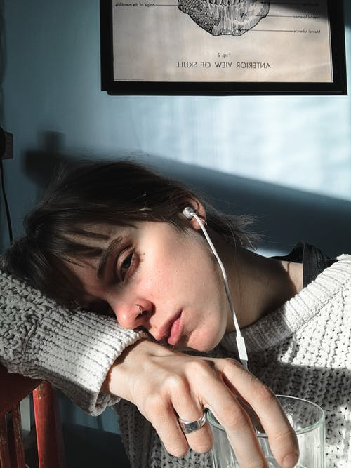 Melancholy female with earphones listening to music and leaning on arm and looking away while sitting with glass in room