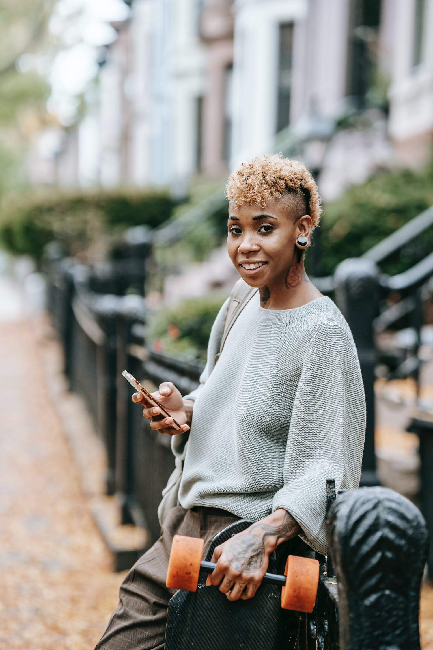 Cheerful black woman with smartphone and dumbbell on street