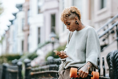 Attentive ethnic woman chatting on smartphone in town