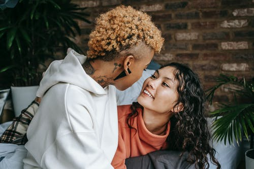 Happy ethnic woman with unrecognizable homosexual black partner at home