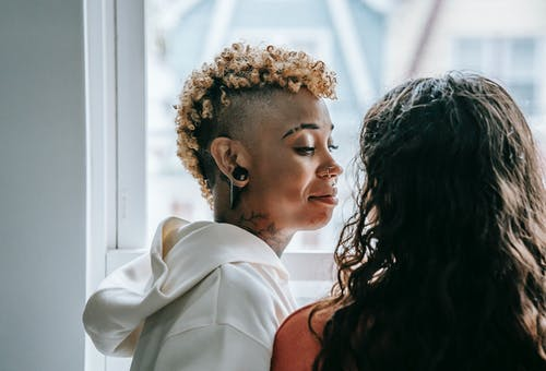 Loving lesbian couple standing together near window