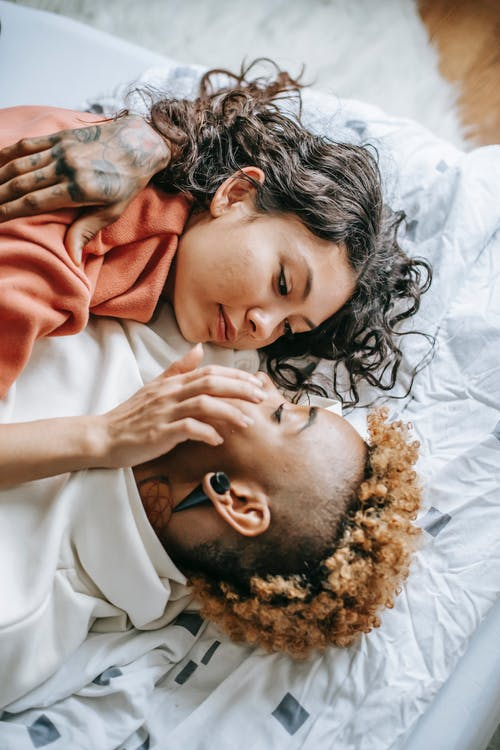 From above young positive multiracial couple embracing on comfortable bed and touching face gently
