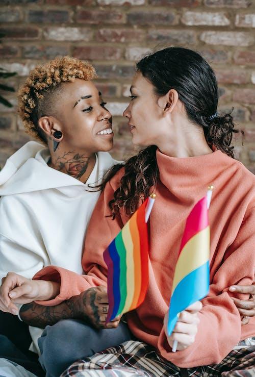 Casal De Lésbicas Multiétnica Alegre Segurando Bandeiras Lgbt Em Casa