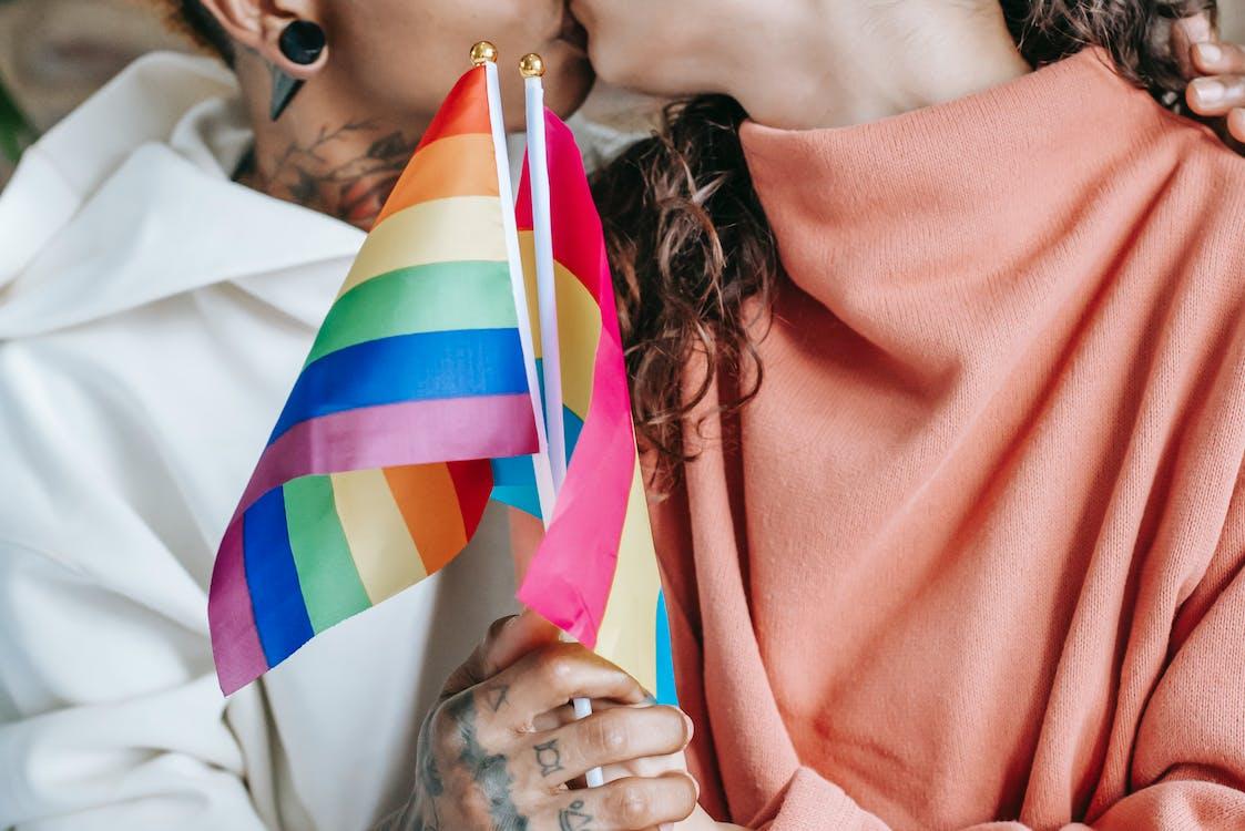 обрезка безликой лесбийской пары, целующейся и сжимающей лгбт флаги