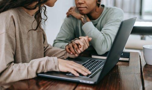 Разнообразная пара с ноутбуком, взявшись за руки