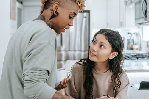 Focused African American female having conversation with Hispanic female while drinking coffee in kitchen