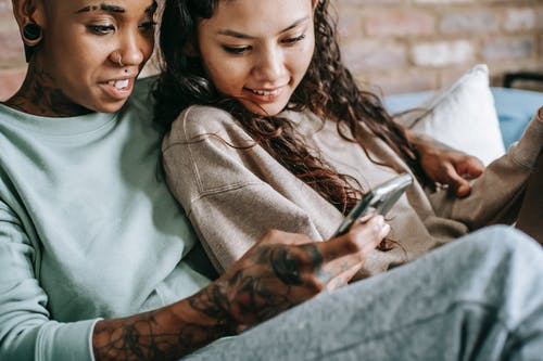 Smiling lesbian couple looking at smartphone on sofa