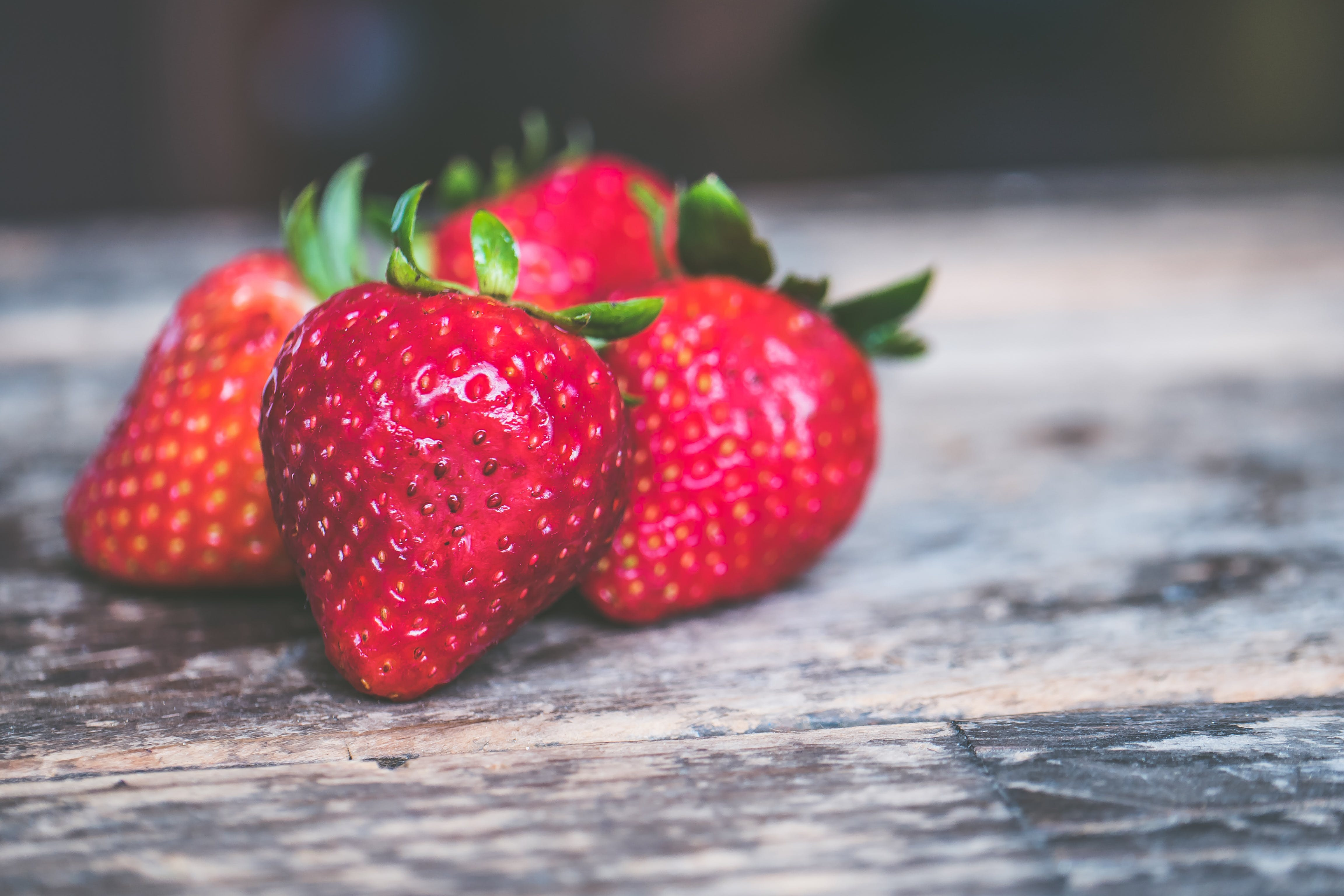 Shallow Focus Photo of Strawberries on Gray Wooden Surface