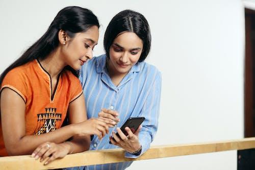 Diverse girlfriends surfing internet on smartphone near wooden fence