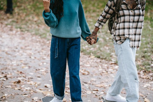 Multiethnic couple holding hands while riding longboards in park