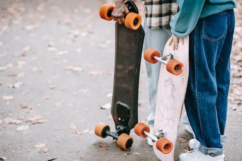 Stylish hipster couple with longboards on asphalt ground