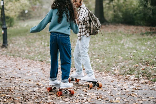 Cheerful diverse same sex couple riding longboards together