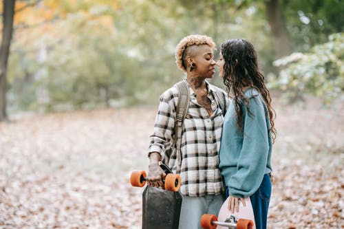 Side view of loving diverse lesbian couple in casual outfits with longboards standing in park and going to kiss