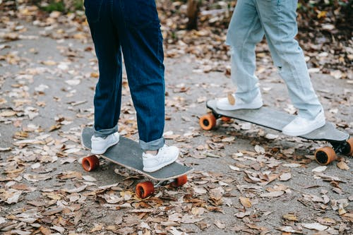 Crop legs of anonymous people in jeans and sneakers riding skateboards on asphalt walkway in park in autumn day