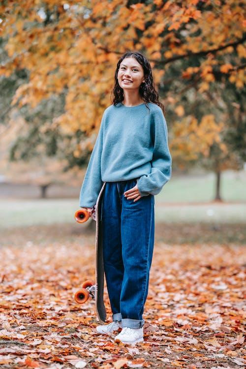 Cheerful woman in autumn park