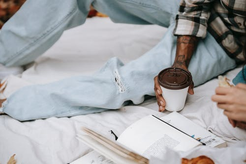Crop unrecognizable ethnic person in jeans and checkered shirt lying on blanket with cup of coffee and book