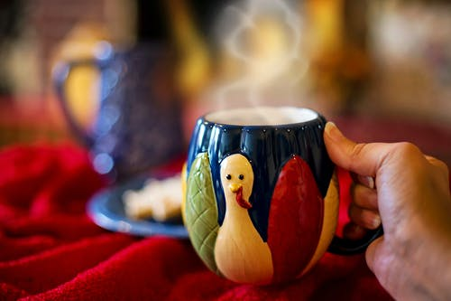 Person Holding White Red and Yellow Ceramic Mug