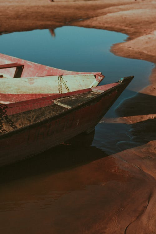 Weathered boats with peeled paint and wooden boards moored on calm water surface of lake near coast in sunny nature