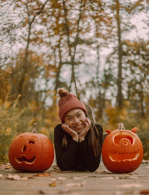 Happy Asian woman lying between carved pumpkins in autumn forest