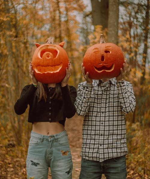 Faceless couple hiding faces behind carved pumpkins in autumn forest