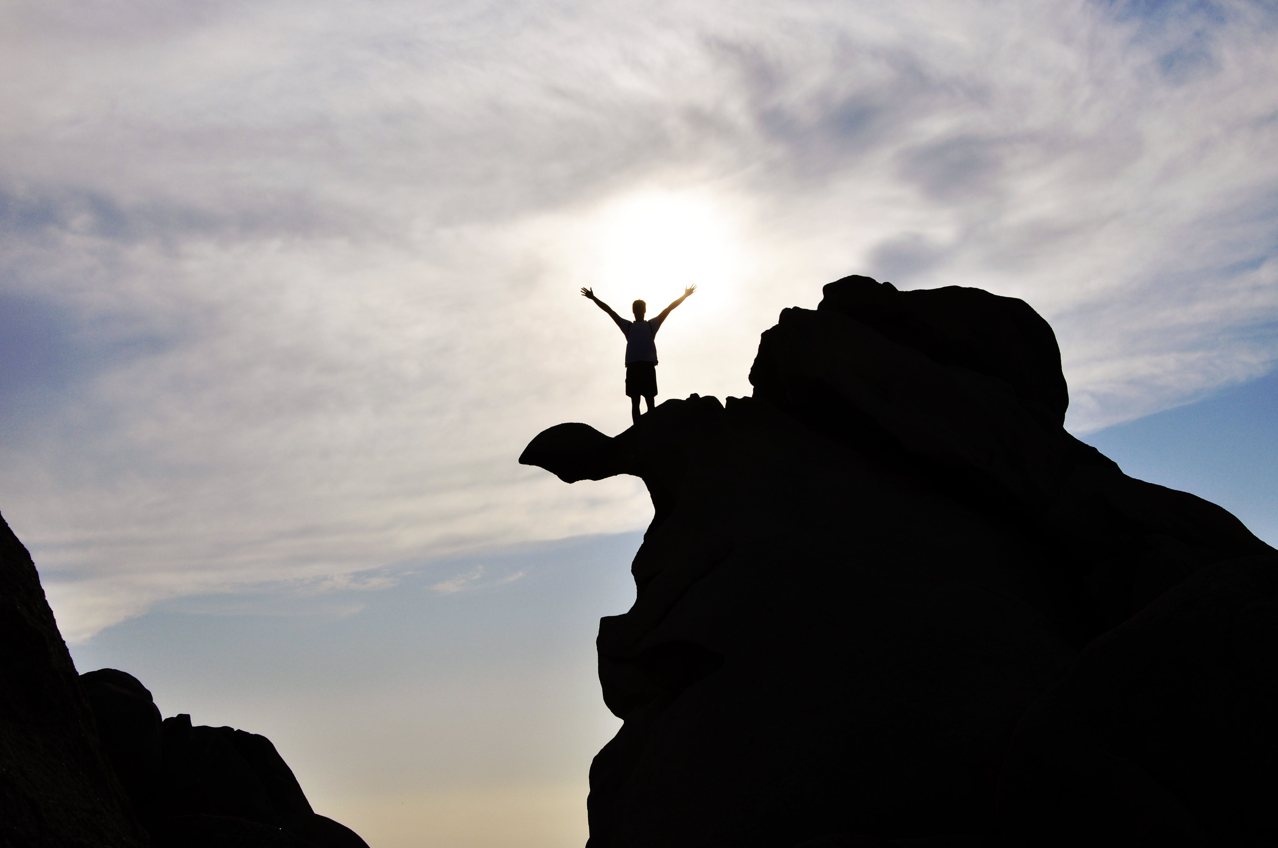 Silhouette Photography of Person Standing on Rock
