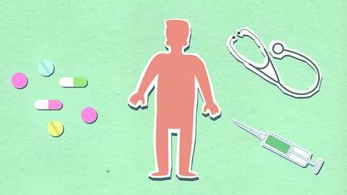 From above of decorative cardboard appliques of person between syringe with stethoscope and medications on green background