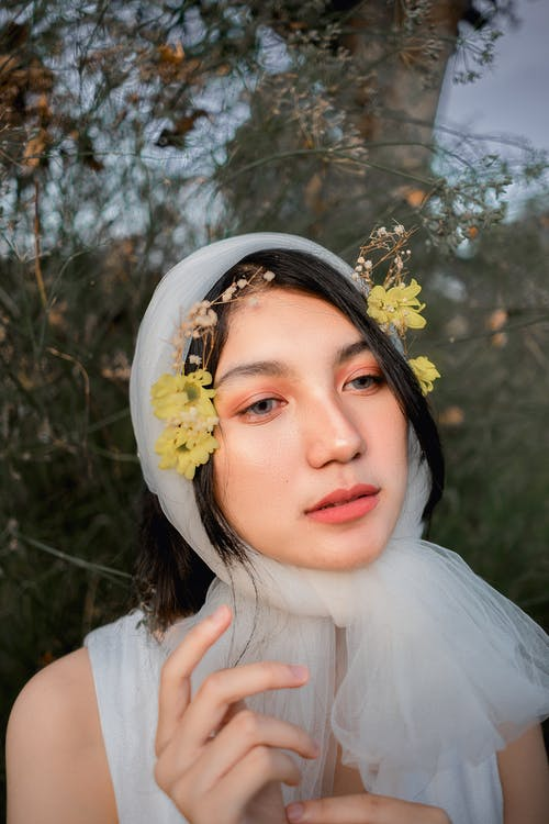Woman in White Shirt With White Flower Headdress