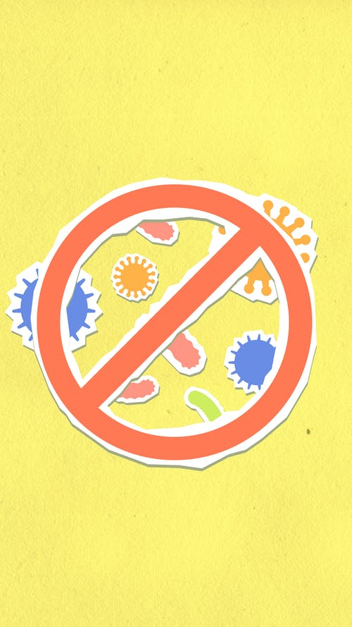 Overhead view of decorative cardboard appliques of prohibition symbol on different viruses and microbes on yellow background