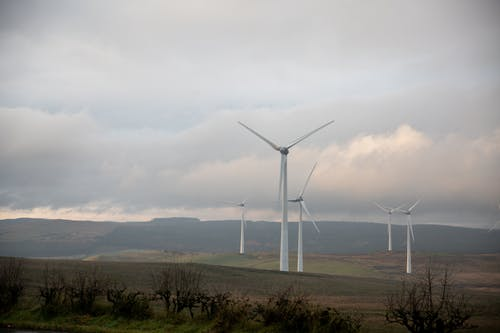 White Wind Turbines on Green Grass Field Under White Cloudy Sky