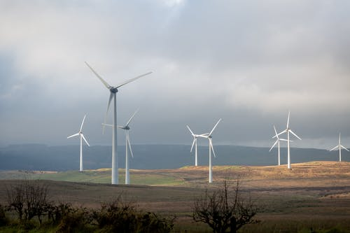 White Wind Turbines on Brown Field Under Gray Cloudy Sky