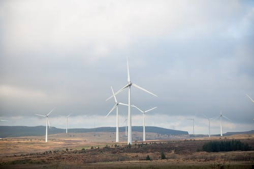 White Wind Turbines on Brown Field Under White Cloudy Sky