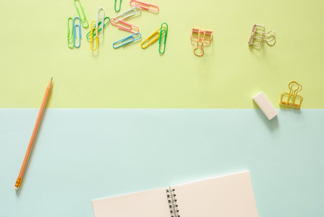 Assorted-color Metal Clips on Table Beside Pencil and Notebook