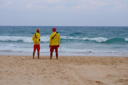 2 Men in Yellow Shirt Standing on Beach