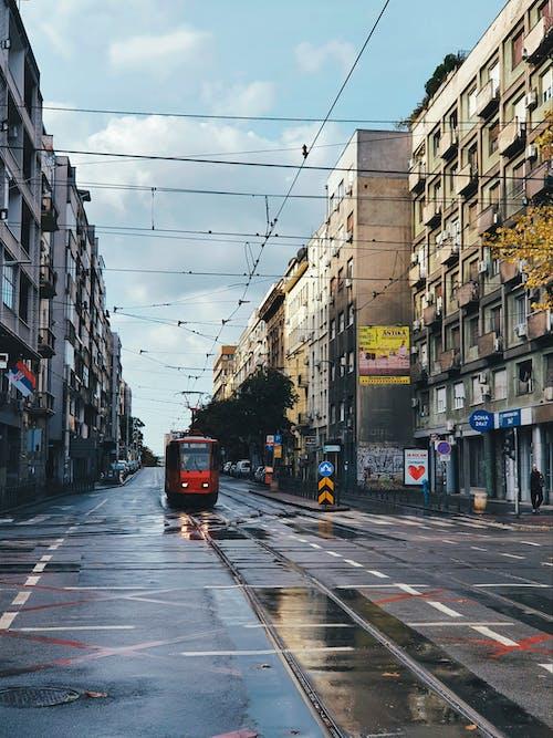 Red and Black Tram on Road Between Buildings